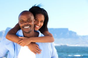 A young healthy attractive couple having fun at the beach. Cape Town's, Table Mountain in the background