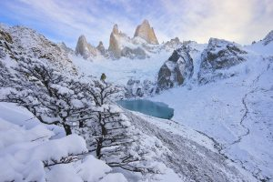A small bird (Gaucho Serrano) contemplates the enormity of Fitz Roy, in Patagonia, which has granite faces of over 4,000 vertical feet, complemented here by fresh snowfall in early winter.