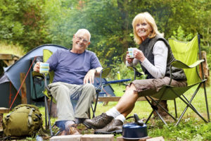 Mature couple enjoying a cup of coffee at their campsite in forest